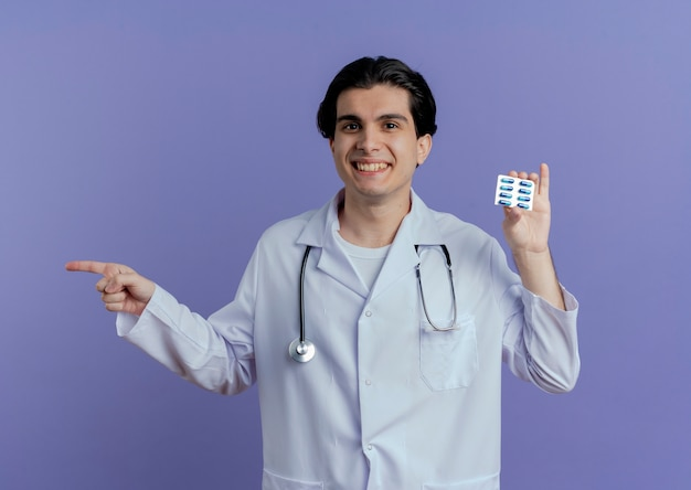 紫色の壁に隔離された側を指しているカプセルのパックを示す医療ローブと聴診器を身に着けている若い男性医師の笑顔