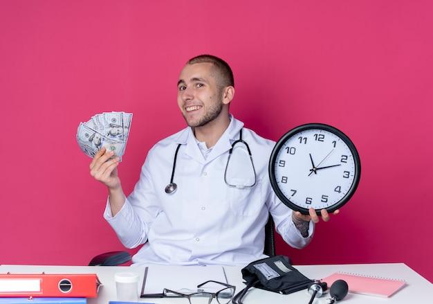 의료 가운과 분홍색 벽에 고립 된 시계와 돈을 들고 작업 도구로 책상에 앉아 청진기를 입고 웃는 젊은 남성 의사