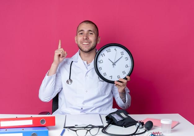 의료 가운과 청진기를 착용하고 시계를 들고 분홍색 벽에 고립 된 손가락을 올리는 작업 도구로 책상에 앉아 웃는 젊은 남성 의사