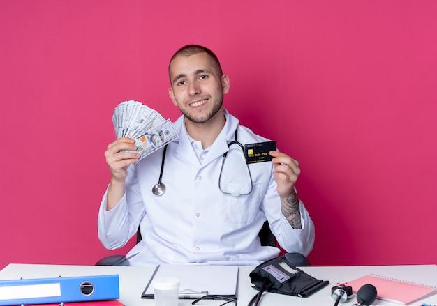 의료 가운과 분홍색 벽에 고립 된 신용 카드와 돈을 들고 작업 도구로 책상에 앉아 청진기를 입고 웃는 젊은 남성 의사