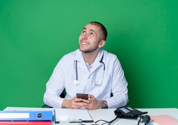 의료 가운과 청진기를 착용하고 작업 도구가 휴대 전화를 들고 녹색 벽에 고립 된 찾고 책상에 앉아 웃는 젊은 남성 의사
