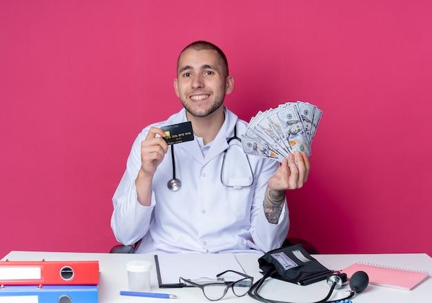 의료 가운과 분홍색 벽에 고립 된 돈과 신용 카드를 들고 작업 도구로 책상에 앉아 청진기를 입고 웃는 젊은 남성 의사