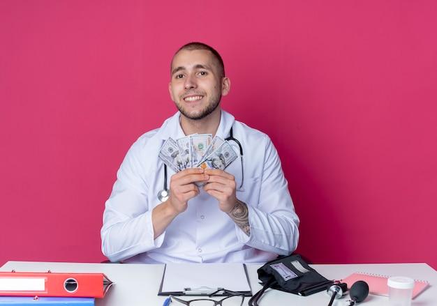 분홍색 벽에 고립 된 돈을 들고 작업 도구로 책상에 앉아 의료 가운과 청진기를 입고 웃는 젊은 남성 의사