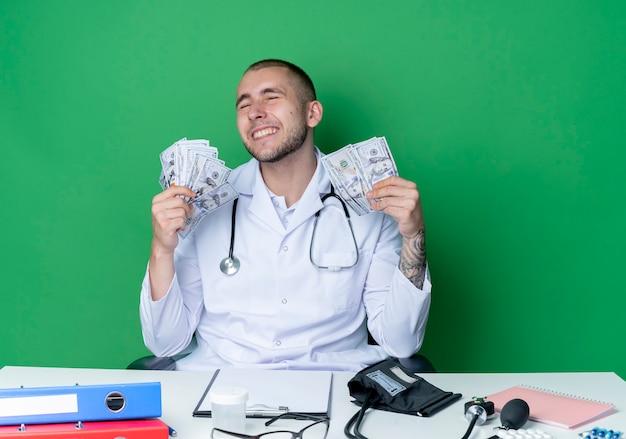 녹색 벽에 고립 된 닫힌 눈으로 돈을 들고 작업 도구로 책상에 앉아 의료 가운과 청진기를 입고 웃는 젊은 남성 의사