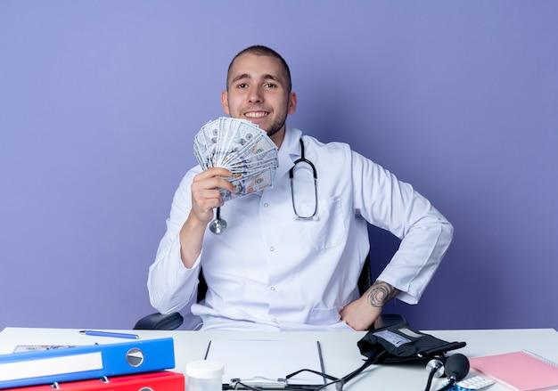 보라색 벽에 고립 된 허리에 손으로 돈을 들고 작업 도구로 책상에 앉아 의료 가운과 청진기를 입고 웃는 젊은 남성 의사