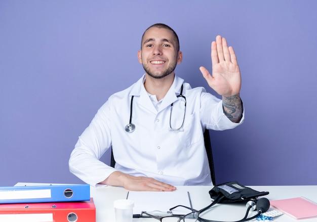 의료 가운과 청진기를 입고 젊은 남성 의사가 책상에 손을 얹고 보라색 벽에 고립 된 앞에서 몸짓을하는 작업 도구로 책상에 앉아 웃고