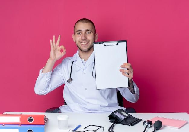의료 가운과 청진기를 착용하고 클립 보드를 표시하고 분홍색 벽에 고립 된 확인 서명을하는 작업 도구로 책상에 앉아 웃는 젊은 남성 의사