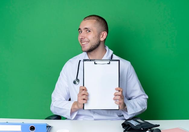 녹색 벽에 고립 된 클립 보드를 보여주는 작업 도구와 책상에 앉아 의료 가운과 청진기를 입고 웃는 젊은 남성 의사