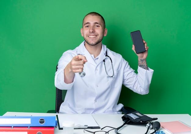 의료 가운과 청진기를 착용하고 휴대 전화를 보여주는 작업 도구와 책상에 앉아 녹색 벽에 고립 된 앞에서 가리키는 웃는 젊은 남성 의사