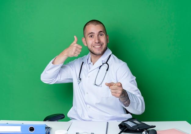 의료 가운과 청진기를 착용하고 엄지 손가락을 보여주는 작업 도구로 책상에 앉아 녹색 벽에 고립 된 앞에서 가리키는 웃는 젊은 남성 의사