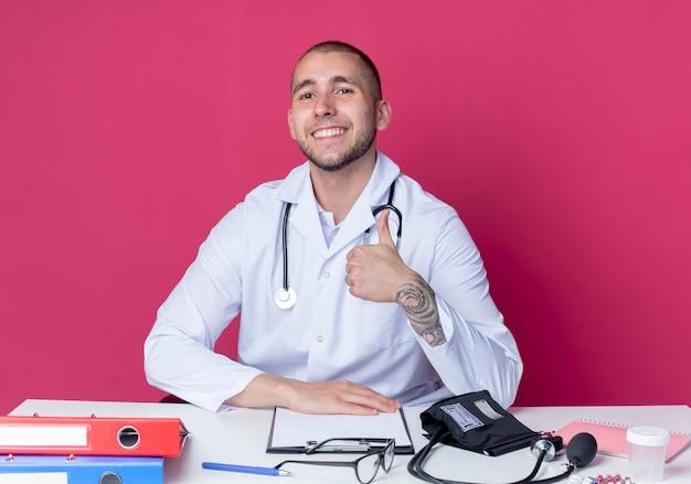 의료 가운과 청진기를 입고 웃는 젊은 남성 의사가 분홍색 벽에 고립 된 엄지 손가락을 보여주는 작업 도구로 책상에 앉아