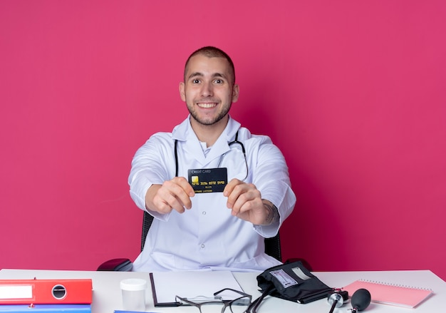 분홍색 벽에 고립 된 전면을 향해 신용 카드를 뻗어 작업 도구로 책상에 앉아 의료 가운과 청진기를 입고 웃는 젊은 남성 의사