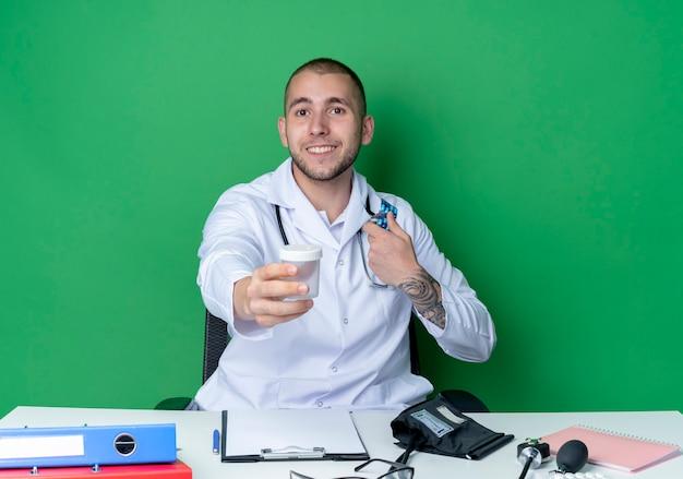 의료 가운과 청진기를 착용하는 젊은 남성 의사가 앞쪽으로 의료 비커를 펴고 녹색 벽에 고립 된 캡슐 팩을 들고 작업 도구로 책상에 앉아 웃고
