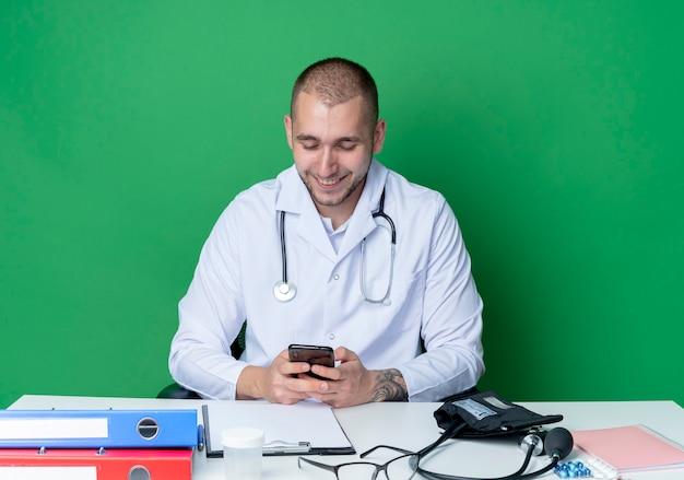 의료 가운과 청진기를 착용하고 작업 도구를 사용하고 녹색 벽에 고립 된 휴대 전화를보고 책상에 앉아 웃는 젊은 남성 의사