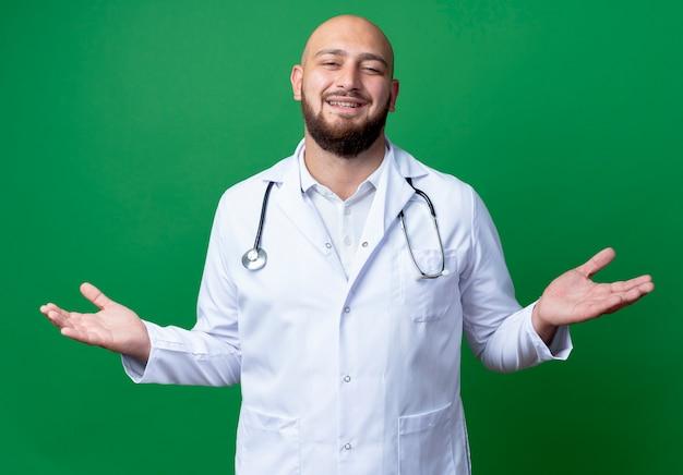 의료 가운과 청진기를 입고 웃는 젊은 남성 의사는 녹색에 고립 된 손을 확산