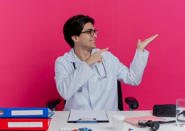 분홍색 벽에 고립 된 측면에서 가리키는 빈 손을 보여주는 측면으로 머리를 돌리는 의료 도구와 책상에 앉아 안경 의료 가운과 청진기를 입고 웃는 젊은 남성 의사