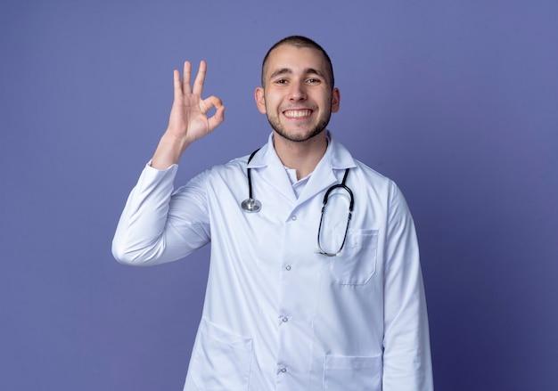 Sorridente giovane medico maschio che indossa veste medica e stetoscopio intorno al collo facendo segno ok isolato sulla parete viola