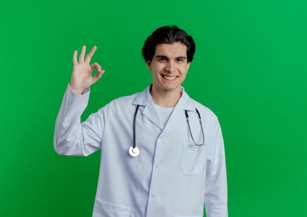 Sorridente giovane medico maschio indossa abito medico e stetoscopio facendo segno ok isolato sulla parete verde con spazio di copia
