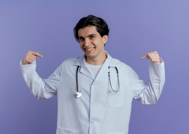 Smiling young male doctor wearing medical robe and stethoscope  and pointing at himself isolated on purple wall