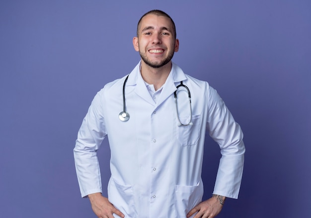 Smiling young male doctor wearing medical robe and stethoscope putting hands on waist isolated on purple wall