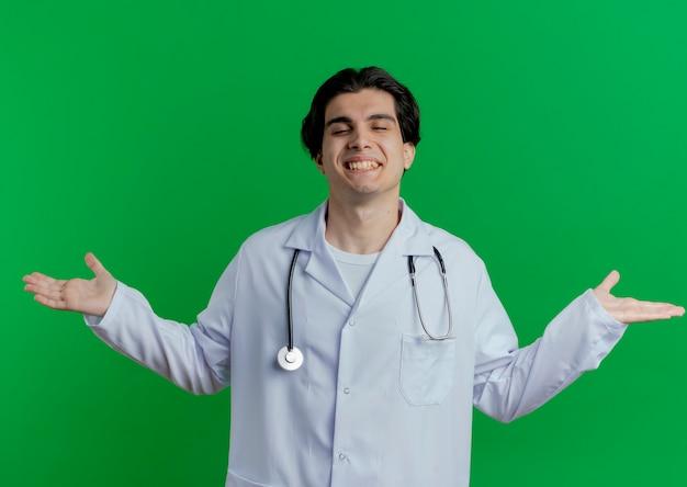 Sorridente giovane medico maschio indossa abito medico e stetoscopio che mostra le mani vuote con gli occhi chiusi isolati sulla parete verde