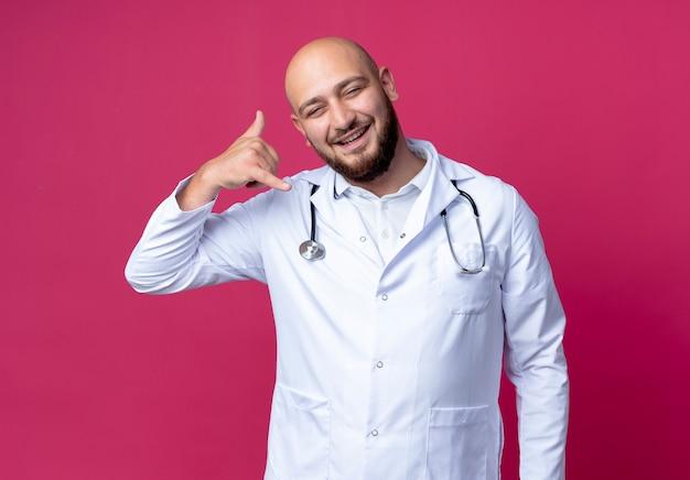 Sorridente giovane medico maschio indossa abito medico e stetoscopio che mostra telefonata