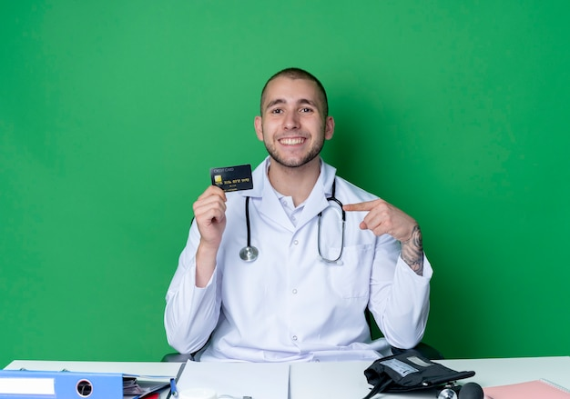 Smiling young male doctor wearing medical robe and stethoscope sitting at desk with work tools holding and pointing at credit card isolated on green wall