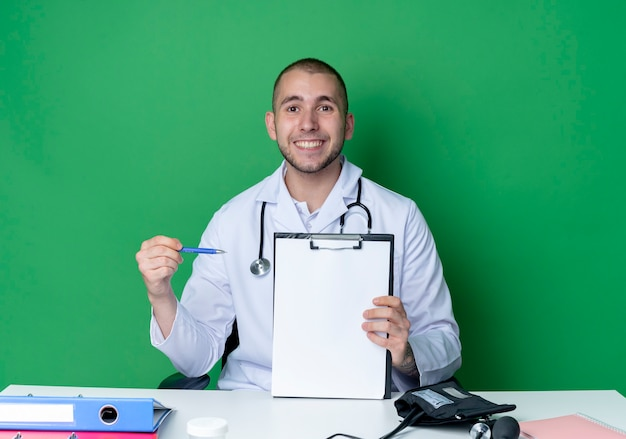 Smiling young male doctor wearing medical robe and stethoscope sitting at desk with work tools holding and pointing with pen at clipboard isolated on green wall