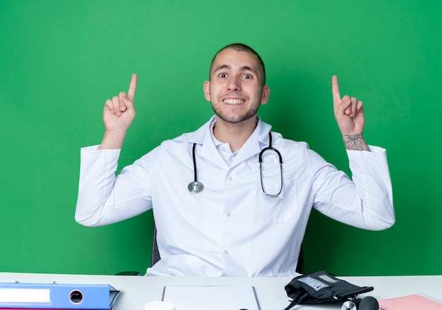 Smiling young male doctor wearing medical robe and stethoscope sitting at desk with work tools pointing up with fingers isolated on green wall