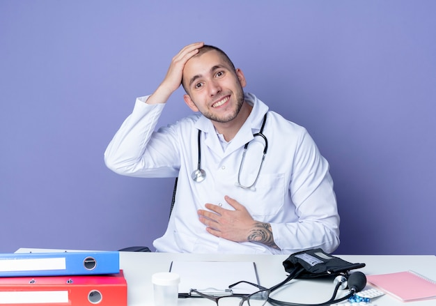 Smiling young male doctor wearing medical robe and stethoscope sitting at desk with work tools putting hands on belly and head isolated on purple wall