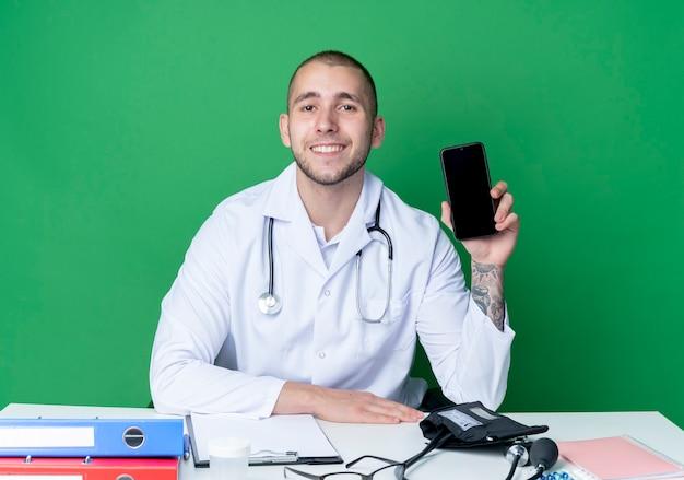 Sorridente giovane medico maschio indossa abito medico e stetoscopio seduto alla scrivania con strumenti di lavoro che mostra il telefono cellulare mettendo la mano sullo scrittorio isolato sulla parete verde