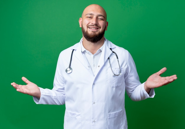 Smiling young male doctor wearing medical robe and stethoscope spreads hands isolated on green