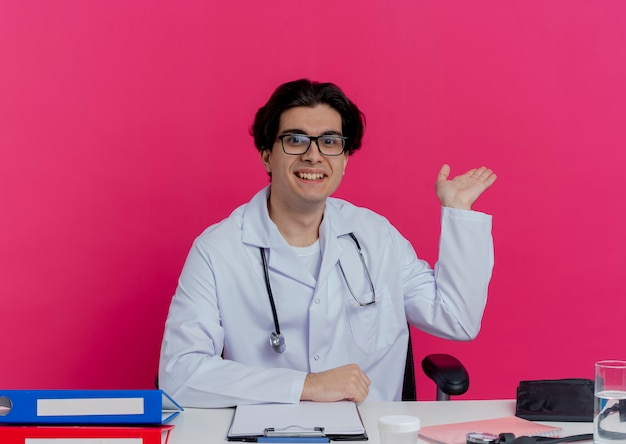 Smiling young male doctor wearing medical robe and stethoscope with glasses sitting at desk with medical tools  showing empty hand isolated on pink wall