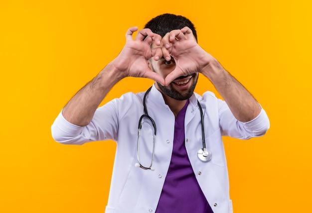 Улыбающийся молодой мужчина-врач в медицинском халате со стетоскопом показывает жест сердца на изолированном желтом фоне