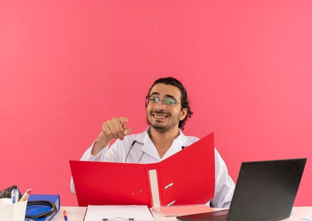 Sorridente giovane medico maschio con occhiali medici che indossano accappatoio medico con stetoscopio seduto alla scrivania