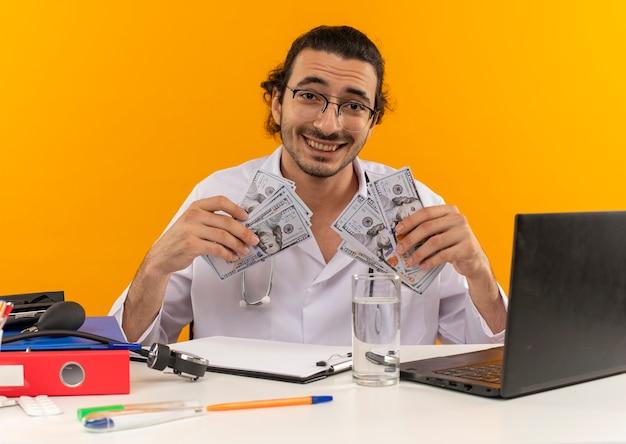 Sorridente giovane medico maschio con occhiali medicali indossando abito medico con stetoscopio