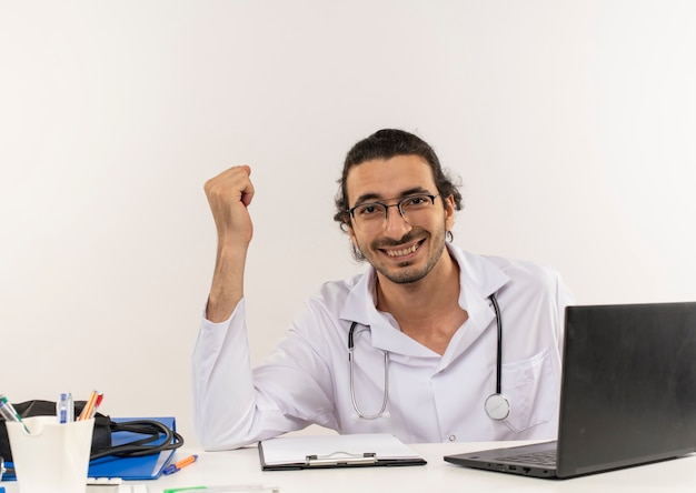 Smiling young male doctor with medical glasses wearing medical robe with stethoscope