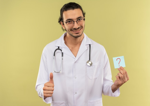 Smiling young male doctor with optical glasses wearing white robe with stethoscope holding paper question mark his thumb up on isolated green wall with copy space
