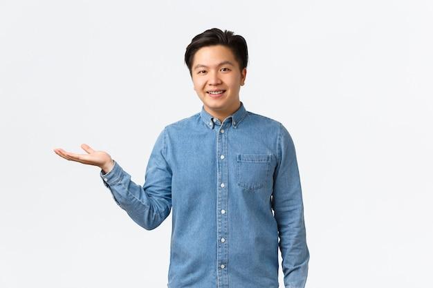 웃고 있는 젊은 남성 기업가가 자신의 사업을 시작하여 무언가를 보여주고, 손에 있는 제품을 보여주고, 왼쪽 팔을 가리키고, 흰색 배경 위에 항목을 소개하거나 링크를 연결합니다.