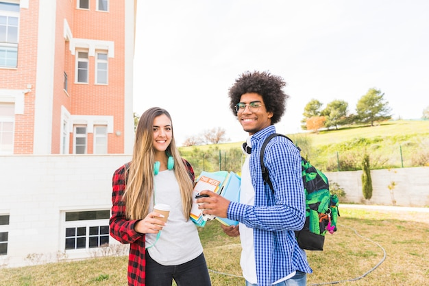 Smiling young male and female students holding takeaway coffee cup and books in hand standing at campus
