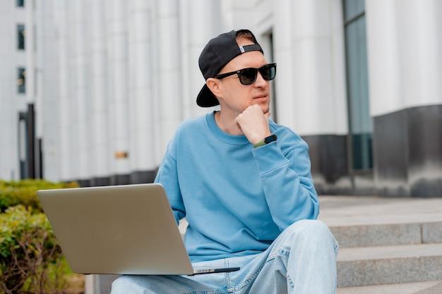 현대적인 복장을 한 웃고 있는 젊은 남성 프리랜서는 노트북과 커피를 들고 계단 밖에 앉아 있다