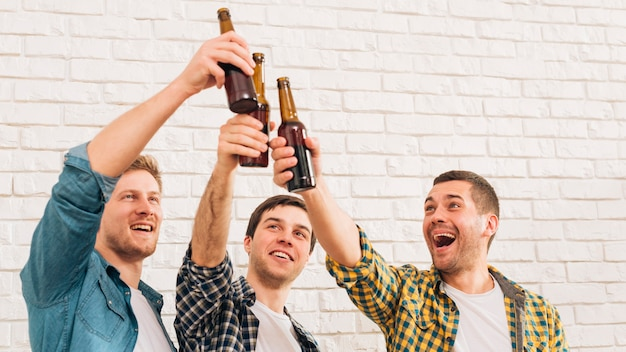 Smiling young male friends standing against white wall raising toast