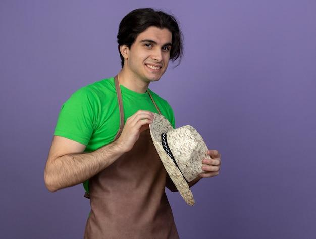 コピースペースと紫に分離されたガーデニング帽子を保持している制服を着た若い男性の庭師の笑顔