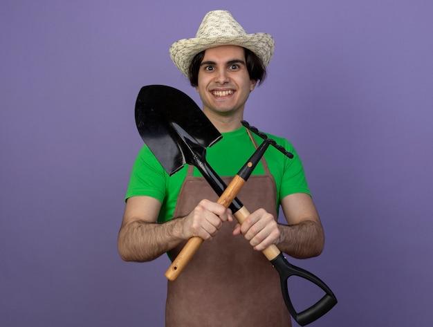 원예 모자를 들고 스페이드와 갈퀴를 건너 제복을 입은 젊은 남성 정원사 미소