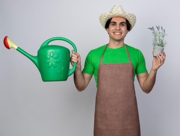 화분에 꽃과 물을 수 들고 원예 모자를 쓰고 제복을 입은 젊은 남성 정원사 미소