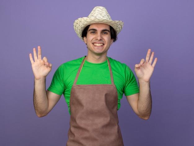 大丈夫なジェスチャーを示すガーデニング帽子をかぶって制服を着た若い男性の庭師の笑顔