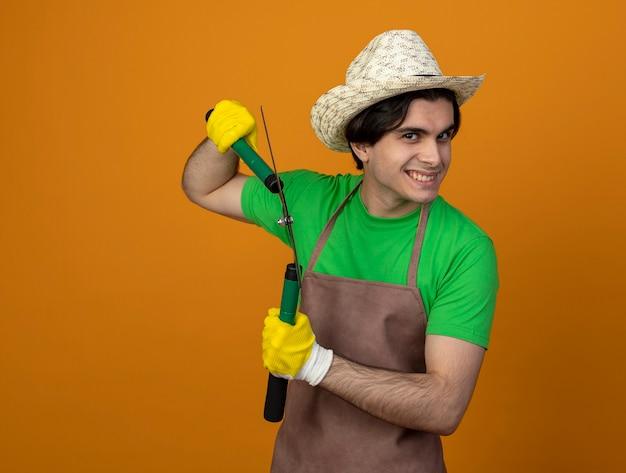 복사 공간 오렌지에 고립 된 가위를 들고 장갑과 원예 모자를 쓰고 제복을 입은 젊은 남성 정원사 미소