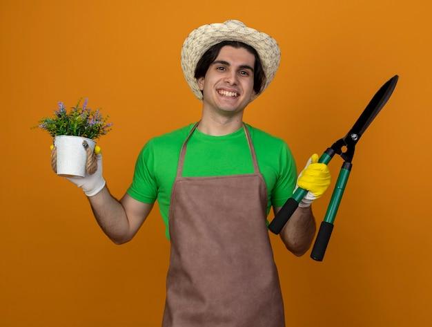 オレンジ色に分離された植木鉢の花とクリッパーを保持している手袋と園芸帽子を身に着けている制服を着た若い男性の庭師の笑顔