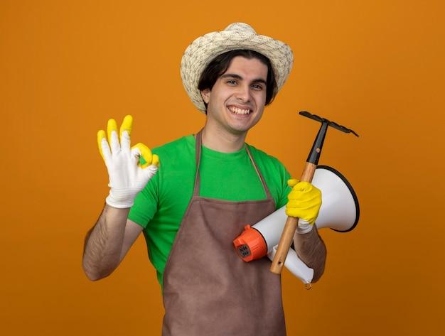 オレンジ色に分離されたはいジェスチャーを示す熊手とスピーカーを保持している手袋と手袋を着用した制服を着た若い男性の庭師の笑顔