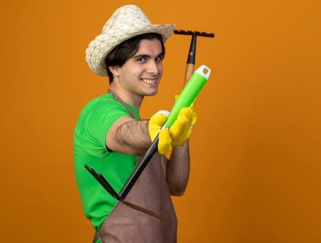 熊手を保持しているくわ熊手を保持している手袋と園芸帽子を身に着けている制服を着た若い男性の庭師の笑顔